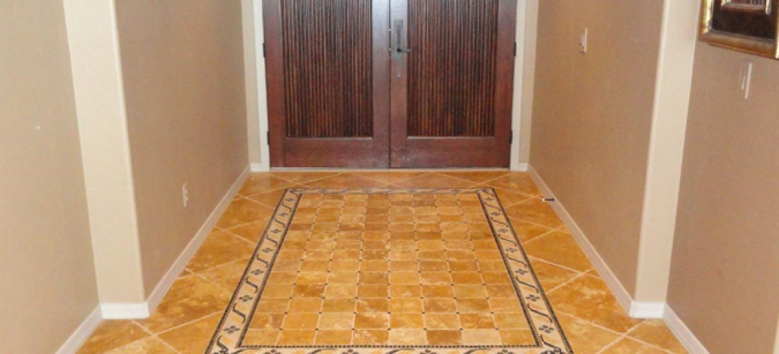 Chiseled-travertine-floor-tile,-with-rug-pattern-mosaic-tile-in-foyer,-tucson